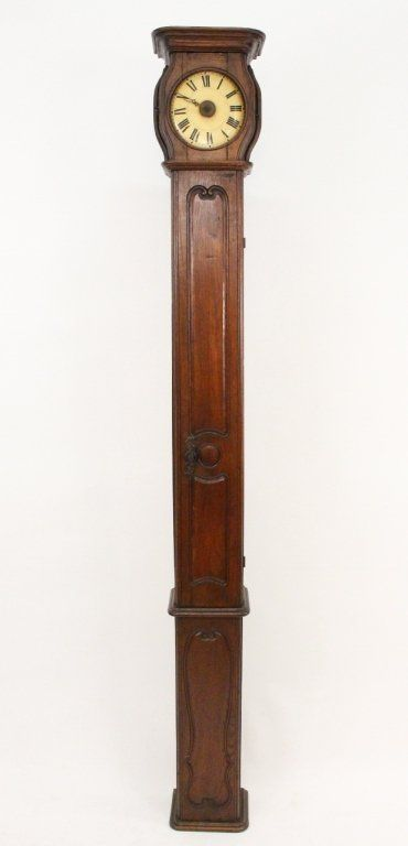 "French, 18th century. Provincial or country tall stained oak cased clock with thin body with scrolled carved borders. Circular cream colored clock face with black Roman numeral dial above center section with hinged door. Height 98"", width 12.5"", depth 9""."