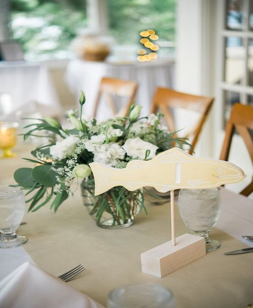 Carved wooden fish served as table numbers  {Ashley Largesse Photography}