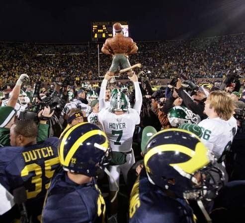 Michigan State Qb Brian Hoyer Holds Up The Paul Bunyan Trophy As Michigan Players File Off The Field Msu Spartans Football Michigan State Football Msu Football