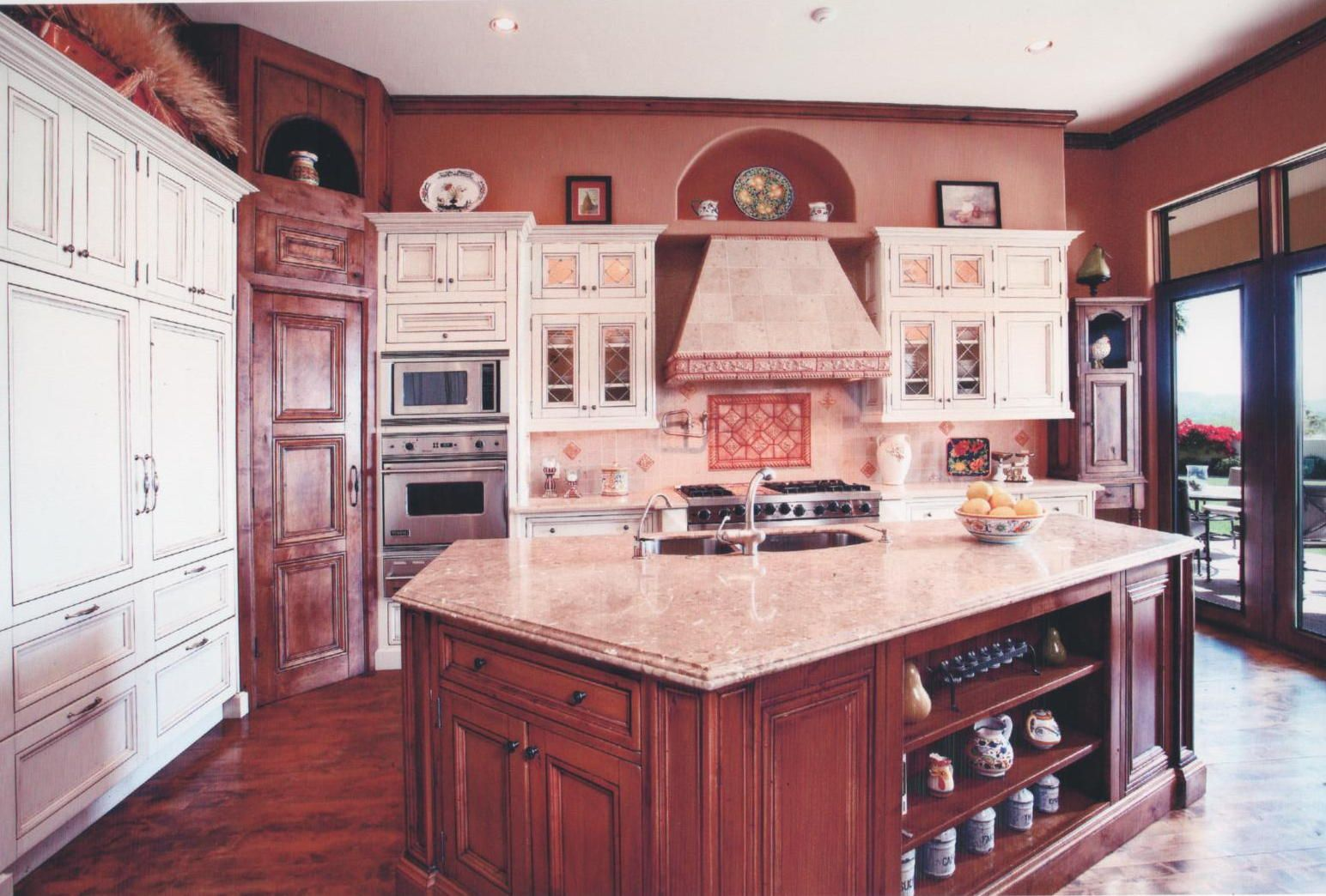 French styling creates a cozy kitchen with warm wood tones and glazed cabinet mixture.