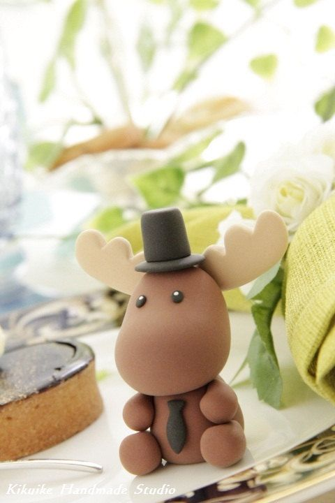 Cute moose only a little baby version maybe with a party hat .. Made of fondant as a cake topper