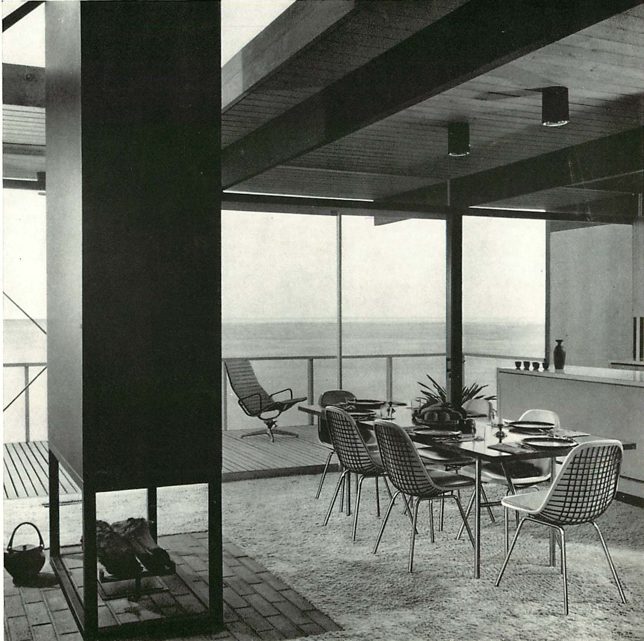 A great modern interior, with Eames Upholstered Wire Chairs inside, and Eames aluminum group outside.