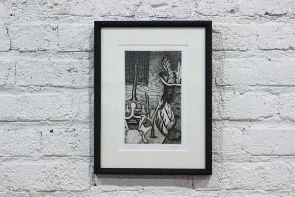 Framed black and white print of leaves and vessel