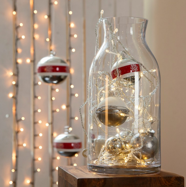 glass vase filled with christmas lights and ornaments  deco