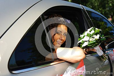 The bride with a wedding bouquet in the car