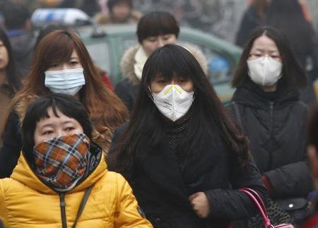 7月23日、中国北京市は大気汚染対策として大規模な石炭火力発電所を閉鎖した。写真は濃霧の中を通勤する人。北京で2月撮影(2014年 ロイター/Kim Kyung-Hoon)