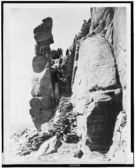 Hopi Indians along steps up rocks, leading to pueblo on mesa, Walpi, Arizona. ca. 1879