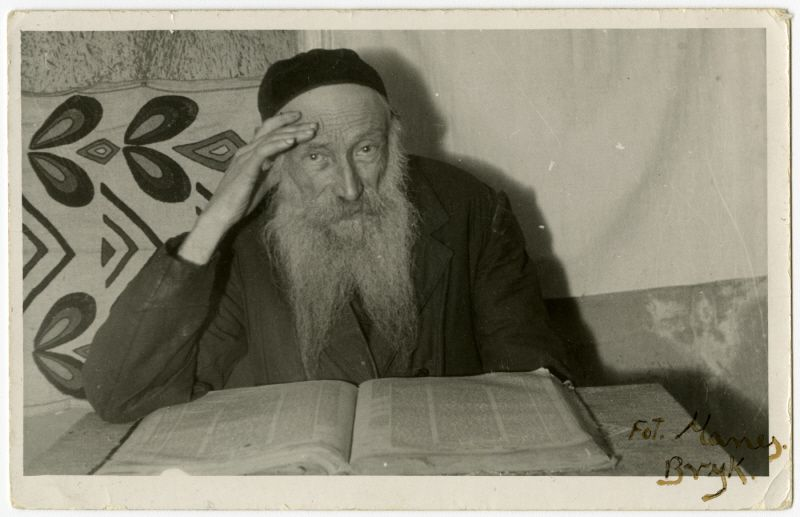 Studio portrait of Reuven Schwartz studying a Jewish text.