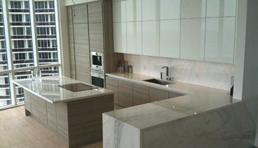 Kitchen designer, Werner Lutz of the Poggenpohl DCOTA showroom, designed this +SEGMENTO kitchen in teak quartz, with polar-white high-gloss lacquer for a condo at the new Trump Tower in Sunny Isles Beach, Florida