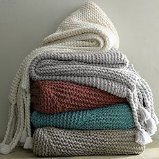 The perfect antidote to a cold evening, this hand-knit blanket keeps you warm and cozies up sofas, chairs and beds with its fringe of long tassels and huggable texture.