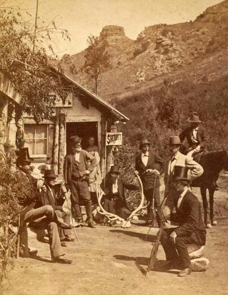 Bakery near Ute Pass by Manitou, Colorado 1877. Belonging to William Iles (the bearded man in the doorway) His daughter Annie is behind him. And the rock formation in the distance is Tim Bunker's Pulpit.