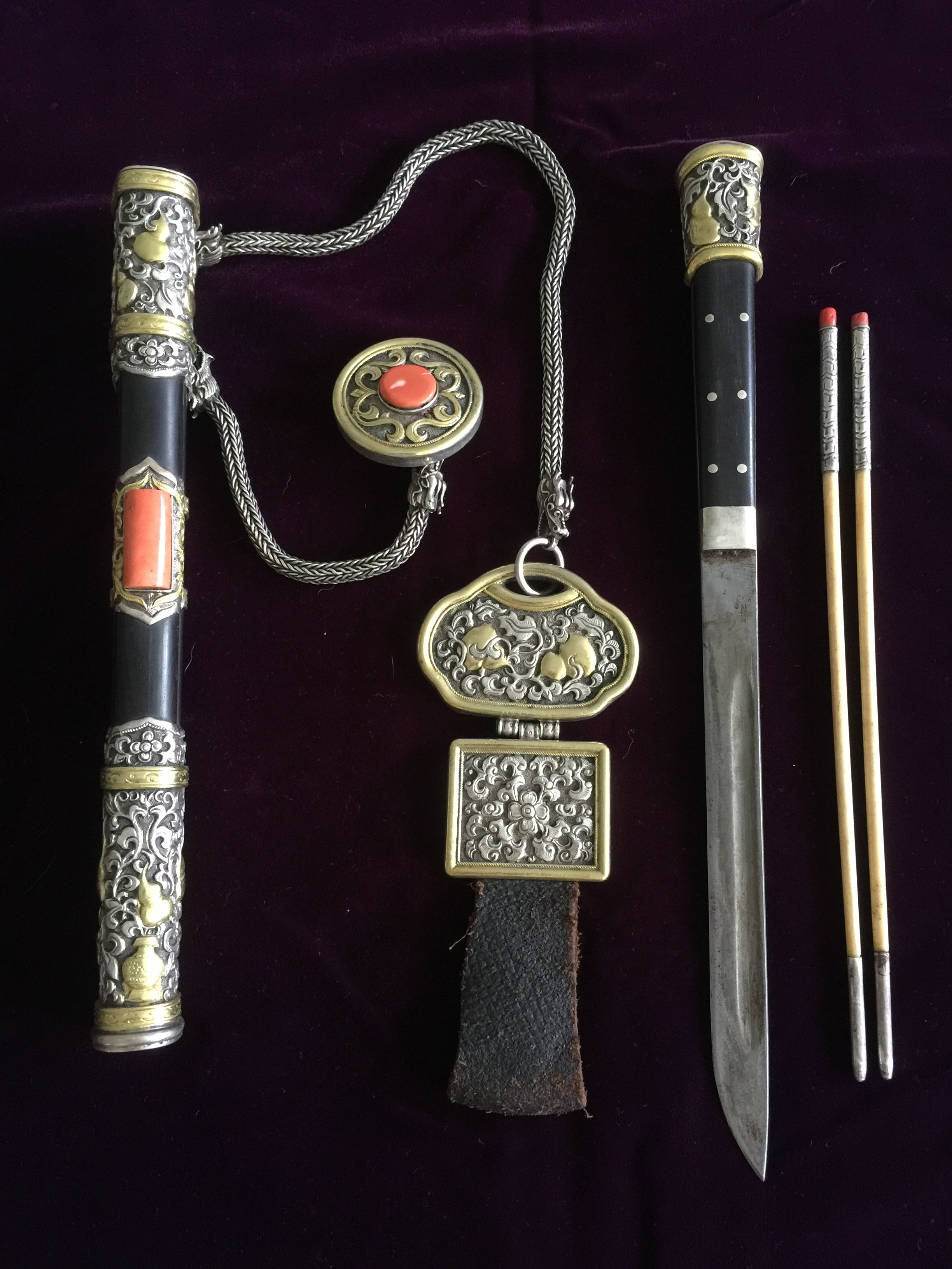 Mongolian knife set, with a pair of ivory chopsticks, a gilt silver and coral toggle and a leather and silver belt pendant. Sheath, belt pendant and knife handle each has gourds and leaves motif on partially gilded silver. 19th c AD