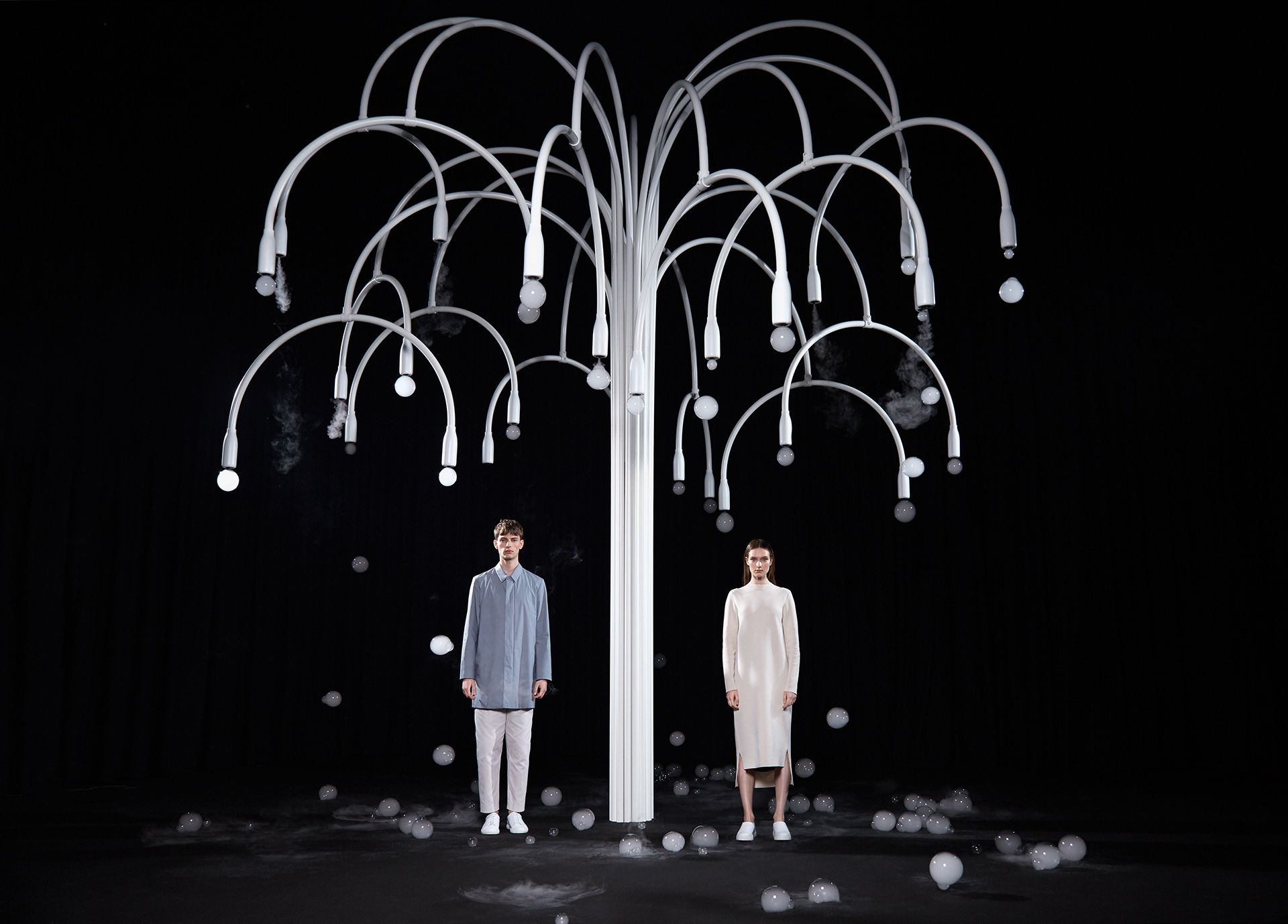 A modernist metal tree stands in a darkened cinema. The New Spring installation plays with the impermanence and the resilience of nature, life, and technology.
