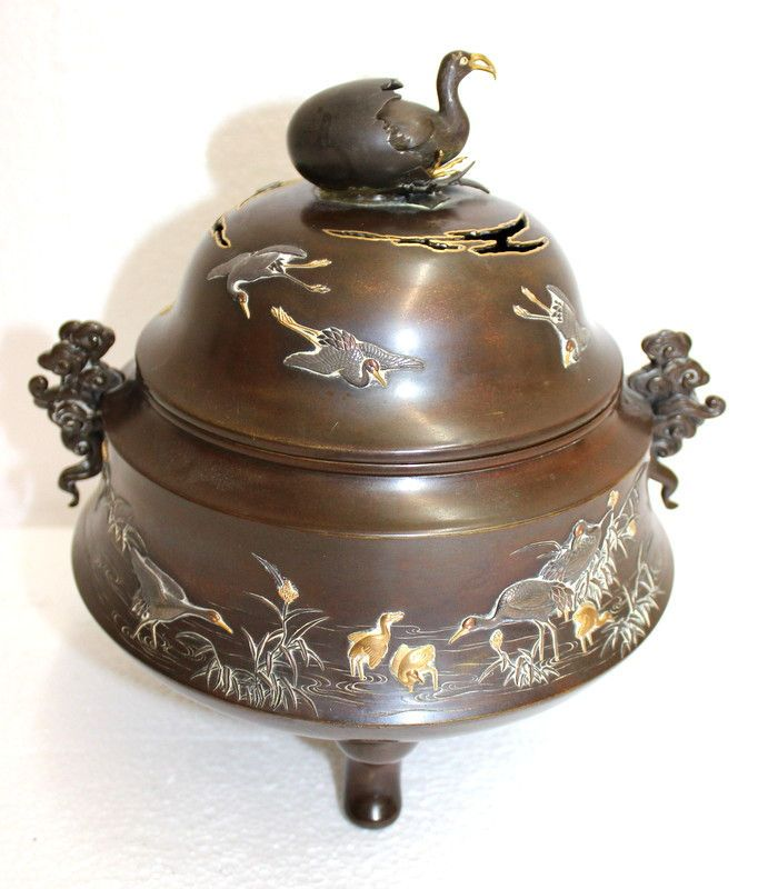 """Antique Japanese Mixed Metal & Bronze Meiji Covered Urn featuring raised cranes across the entire removeable top and body of the footed urn. In both China and Japan, the crane has great importance. It's called the intermediary between earth and heaven. Artist signed on bottom. Measures - 10 1/8"""" high x 8"""" wide."""