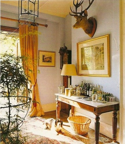 This charming house in Wales is owned by art dealer Guy Morrison and his interior designer wife Penny.> {{The gracious blue front hall is hung with hunting trophies and home to a chicken-wire-panelled French armoire holding a collection of hats and a bar table}}