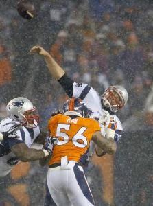 New England Patriots quarterback Tom Brady (12) throws under pressure from Denver Broncos linebacker Shane Ray (56) during the second half of an NFL football game, Sunday, Nov. 29, 2015, in Denver. (AP Photo/Jack Dempsey)