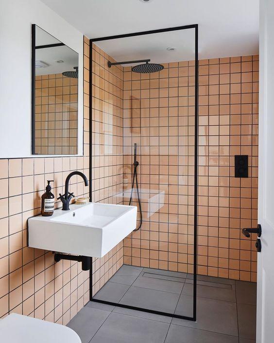 Photo of Badezimmer im Industriestil mit einem femininen Touch. Pfirsichrosa Wandfliesen, gepaart …