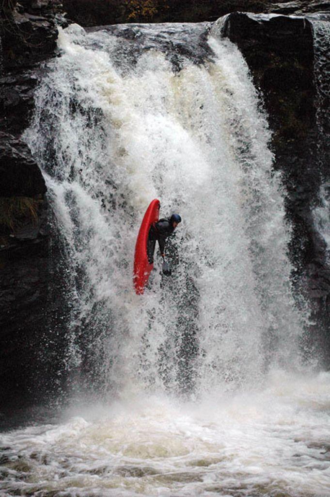 Falloch Falls, preparándose para chuparlo de la cascada de 10 metros en un viaje en kayak en Escocia