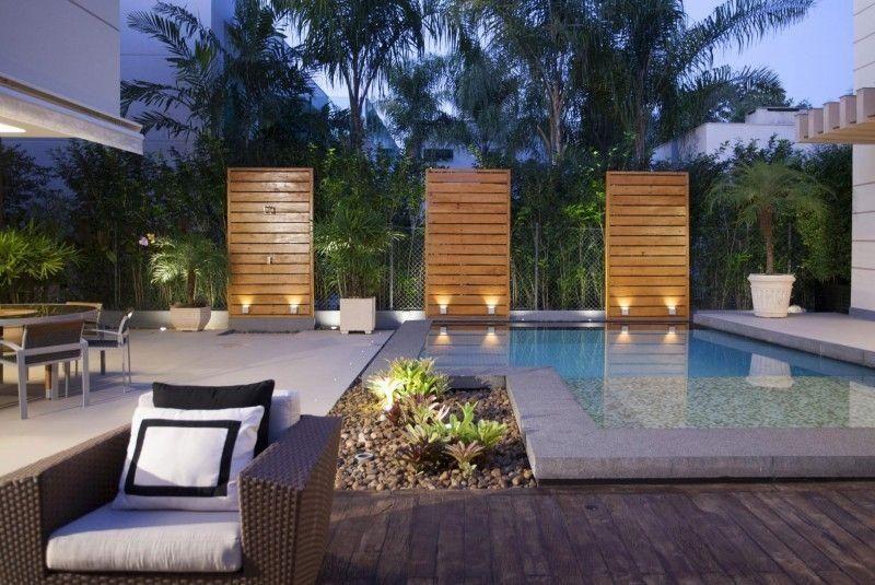 Piscine extérieur élégante brise vue en bois avec appliques murales et petit jardin de