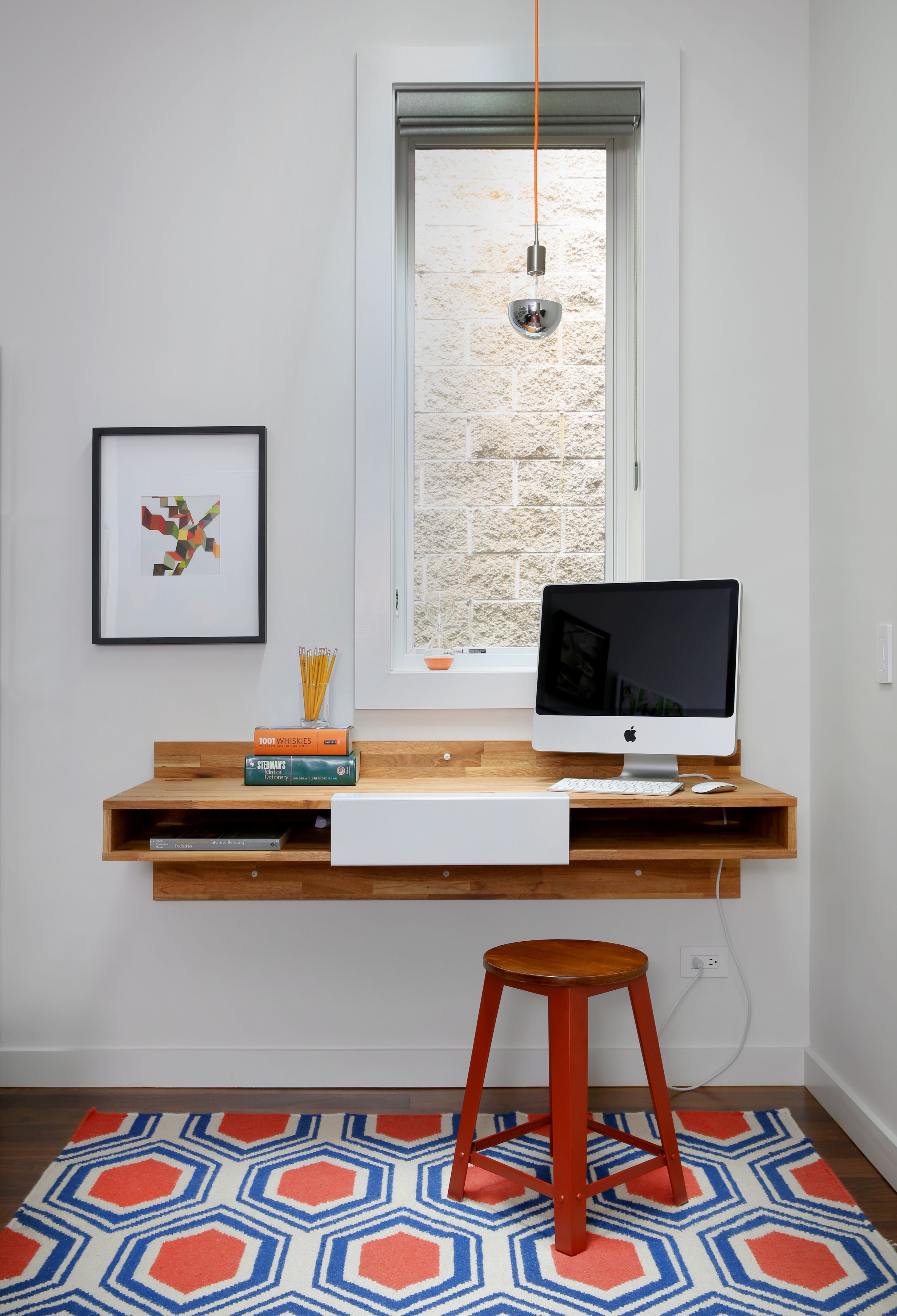 A mash studio wall mounted desk offers a place to study the rug is from one kings lane and a soco modern socket pendant illuminates the room