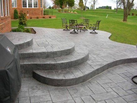 Add Interest To Your Patio A Multi Level Patio Adds A Bit Of Dramatic Flair To A Backyard Stamped Concrete D Concrete Patio Concrete Patio Designs Patio Stairs