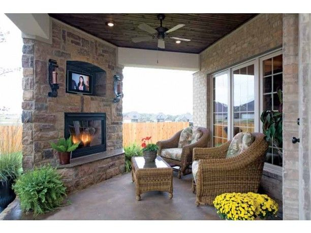 Flat screened tv over fireplace in outdoor dining room for Screened porch fireplace designs
