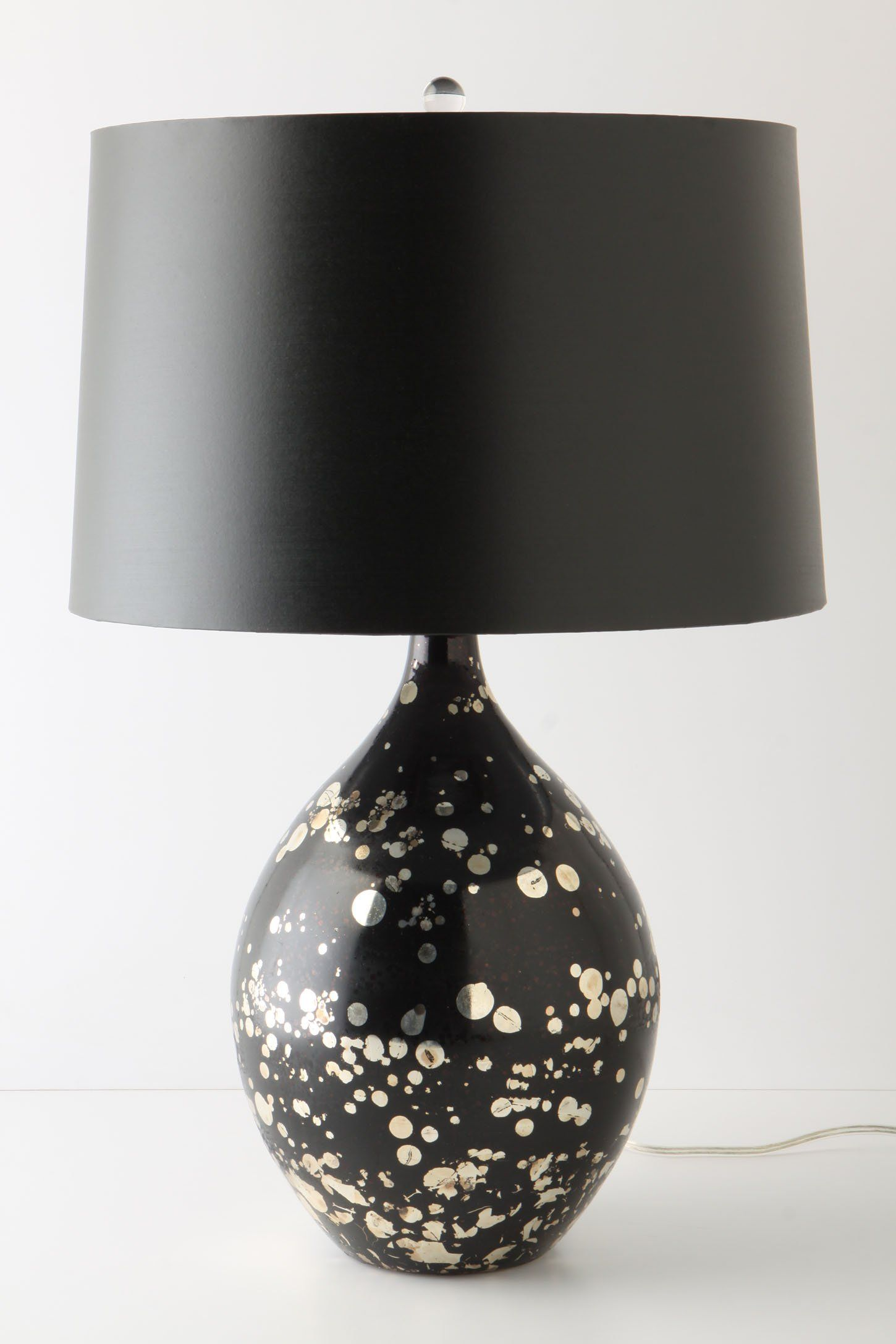 Mouth-blown, gold-splattered black glass is topped with a silver-foil-lined black shade, creating a modern, moody, metallic light source.
