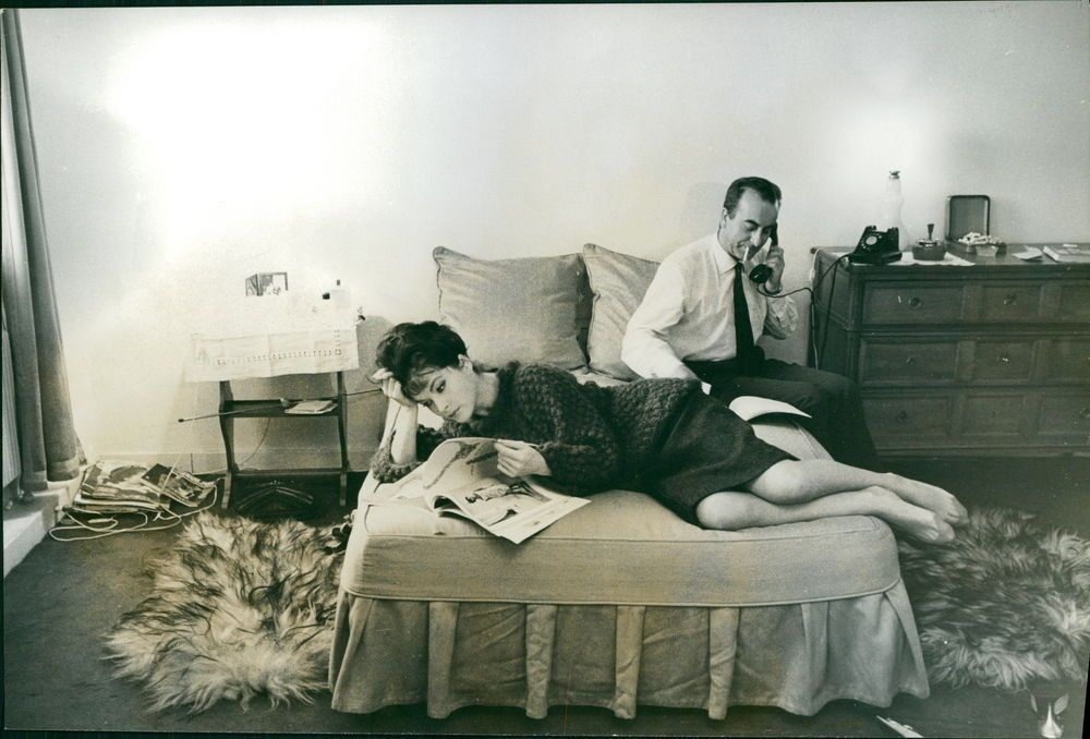 Vintage photo of Yvonne Furneaux relaxing on bed, her husband talking on phone a
