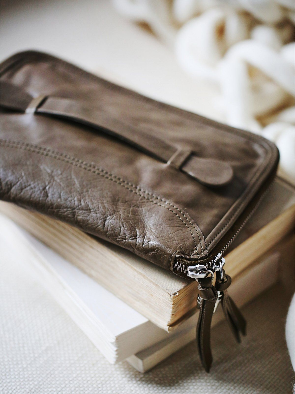 Distressed Travel Wallet   Oversized distressed leather wallet. Minimal designed with a utilitarian leather handle easily works as a clutch. Zip closure.