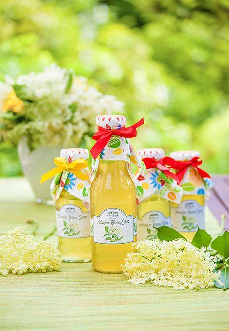 """nur selbstgesammelte Holunterblüten, keine Extrakte oder Aromen kommen in unseren Holunder-Blüten-Sirup. Holunder-Blüten-Sirup haben schon unsere Großmütter im Frühsommer gern gekocht. Diese schöne Tradition war etwas in Vergessenheit geraten – erlebt aber durch das Getränk """"Hugo"""" ein Comeback. Holunder-Blüten-Sirup ist die perfekte Basis für selbstgemachte Limonade. Mischen Sie Sirup und Mineralwasser im Verhältnis 1:7. Somit ergibt ein Liter Sirup insgesamt acht Liter Limonade."""