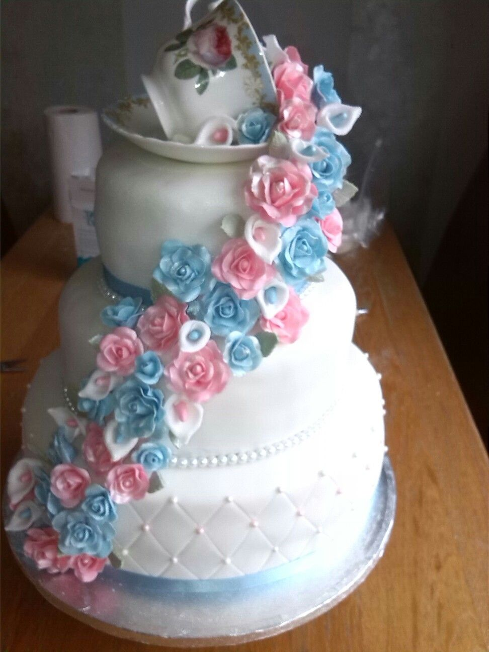 Wedding cake with china teacup and pink and blue roses and lilies