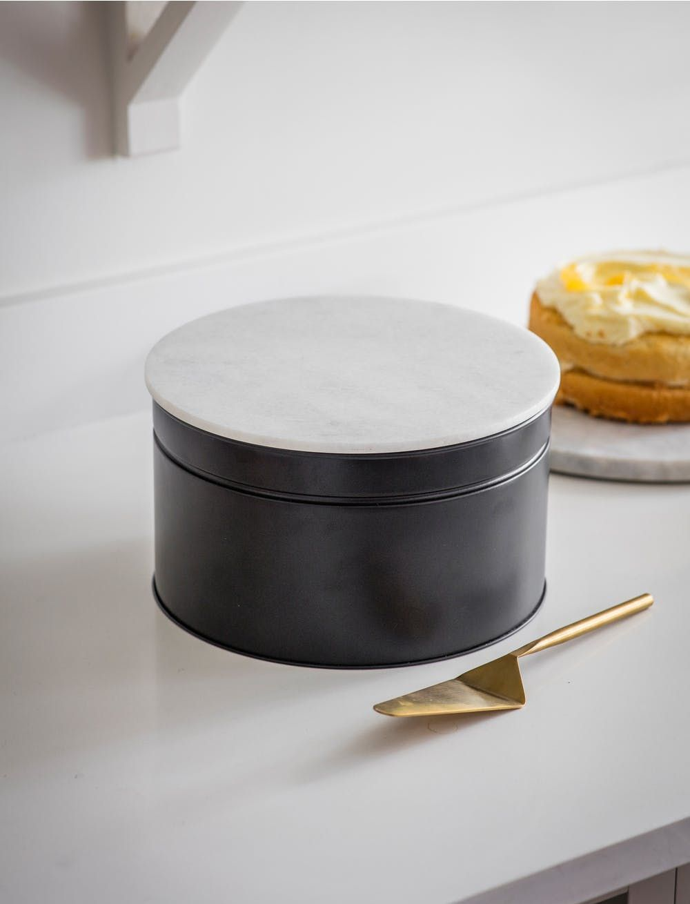 Off Black Circular Metal Brompton 10 Inch Cake Tin With Grey Marble Lid Beside A Brass Cake Slice And Lemon Cake Click To Buy Now Cake Tins Baking Accessories