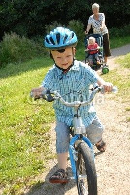 child on bike with grandmother in background