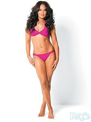 Med henne muskulär kropp och Svart hårtyp utan behå (kupstorlek ) på stranden i bikini