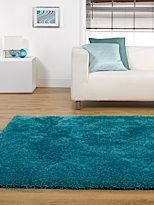 Peacock blue shaggy carpet with white couch.   White rug ...