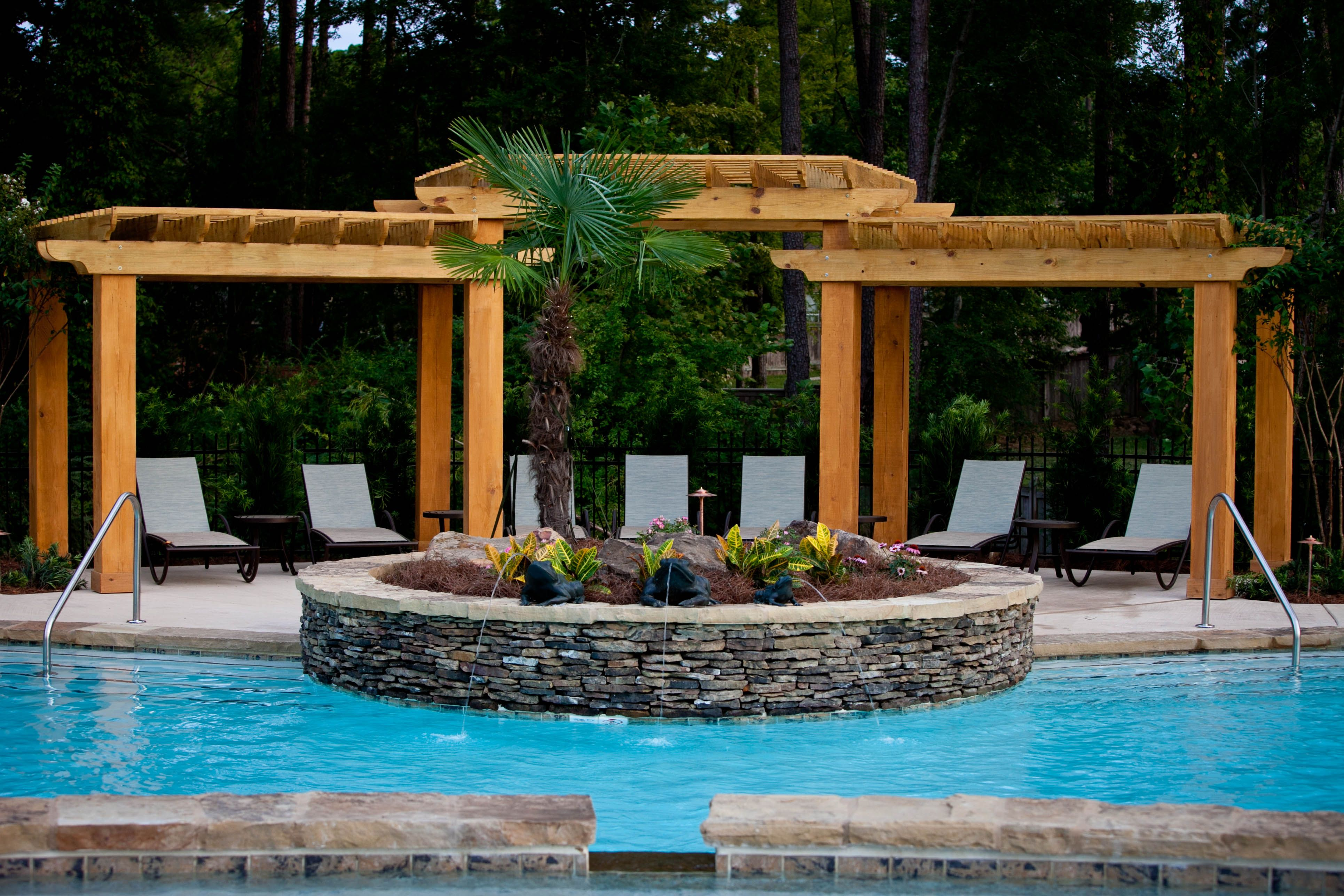 Raised stone planter and arbor next to pool Cool pools