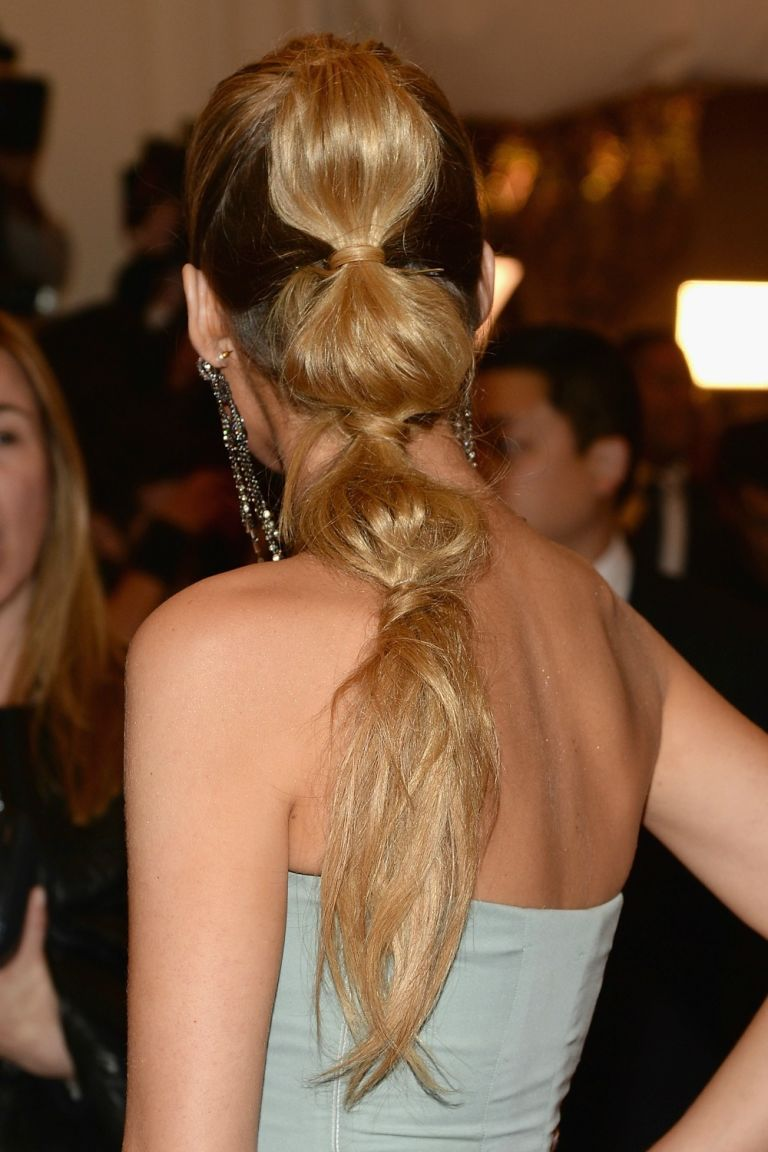 Blake Lively's poufed three-part pony is perfect for a night out. The trick: Gather the top half of your hair into a ponytail at the crown of your head, secure it with an elastic band, and wrap a sliver of hair around it to make it look polished. Then, gather the midsection of your hair and create a pony in between your crown and nape of your neck, wrapping a piece of hair around the elastic to conceal it. Lastly, take the remaining hair and put it into a ponytail, again wrapping the hair…