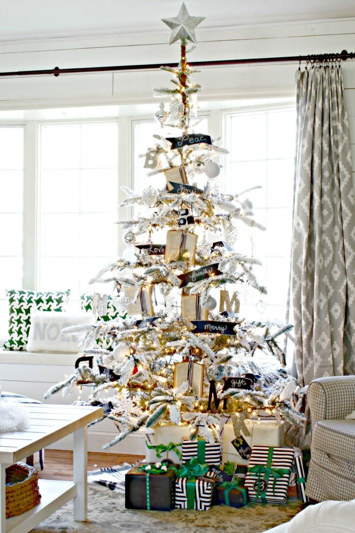 flocked christmas tree decorated with small books black and white accents and mercury glass ornaments wwwgoldenboysandmecom