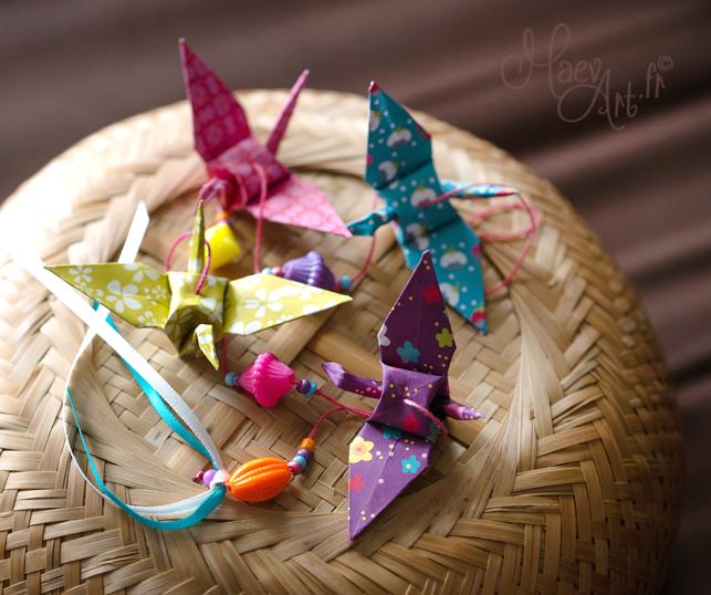 67 cm de longueur. Pliage grues origami en divers papiers à motifs (vert, bleu, rose, violet). Perles en plastique et perles de rocailles. Fil en coton.