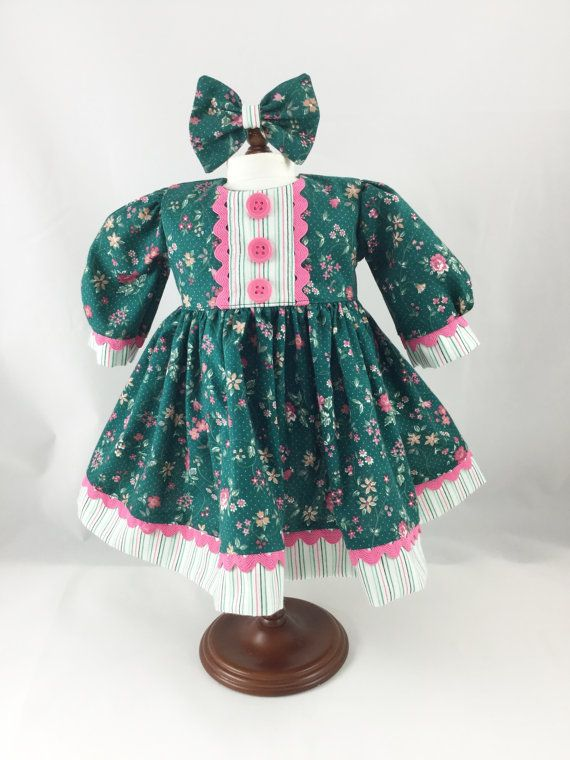 Handmade long sleeved doll dress in a pretty pink and white calico print on a dark green background with coordinating pink, green, and white