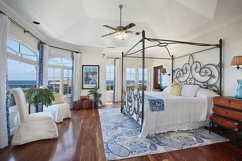 Stunning coastal bedroom with a beautiful four poster iron bed and I love the rug......