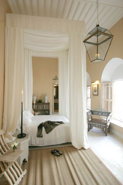 An Airy Light Filled Room With An Opulent Tall Canopy Bed Draped With White  Fabric
