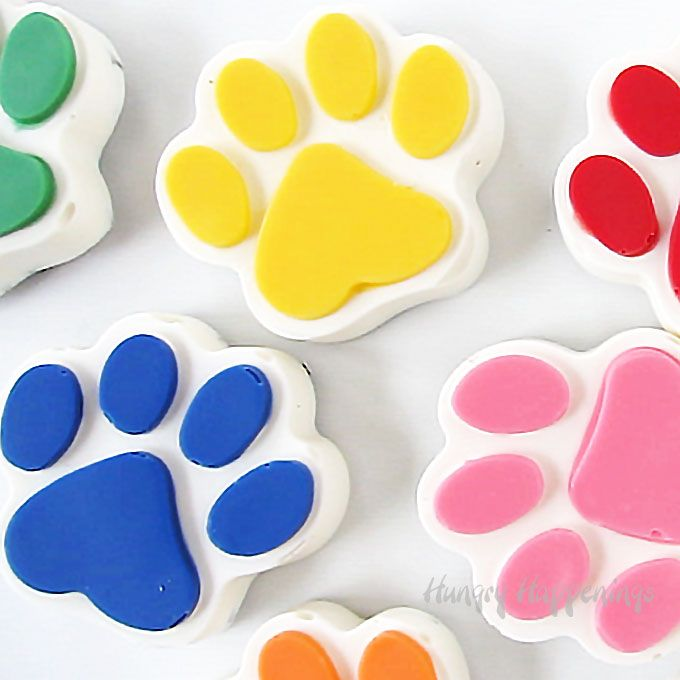 Cookies 'n Cream Paws in Rainbow Paw Patrol Colors - Paw patrol cookies, Paw cookies, Paw patrol cupcake toppers, Paw patrol cake toppers, Paw patrol cake, Paw patrol cupcakes - Rainbow colored white chocolate paws filled with pieces of Oreo Cookies