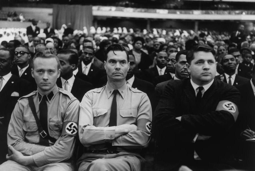 Eve Arnold -  George Lincoln  Rockwell, flanked by members of his American Nazi Party, listening to Malcolm X's speech to black Muslims at the International Amphitheater in Chicago, 1962