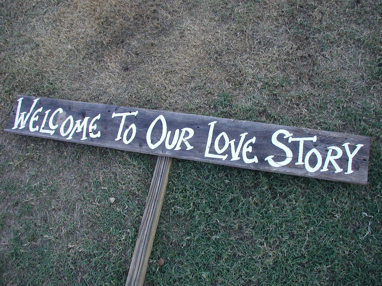 Rustic wood wedding sign on stake welcome to our love story barn