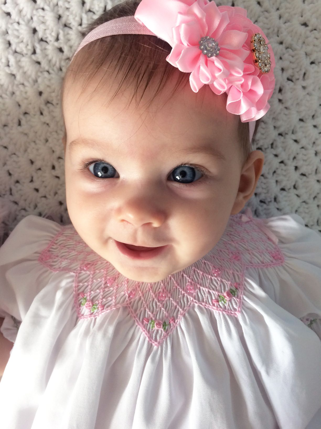 Beautiful baby girls wearing a hand smocked white and pink dress and