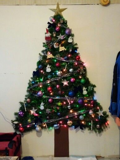 Christmas wall tree. We drew the tree shaped outline on our wall with pencil. The trunk is green ...