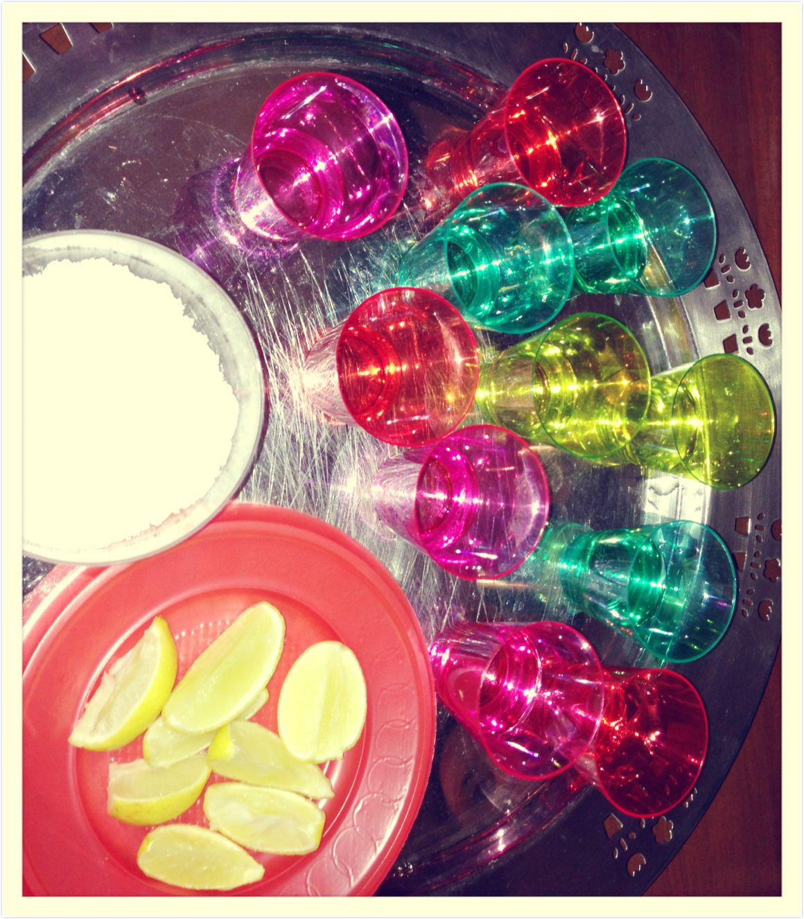 Tequila shots in colored shot glasses & limes