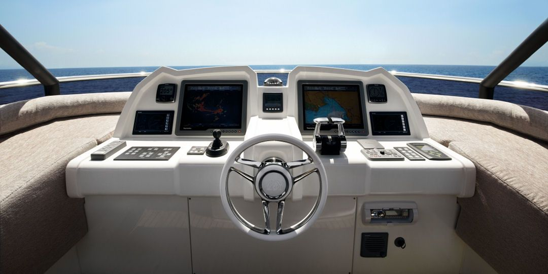 Monte Carlo Yachts 70: This view of the helm on the flying bridge shows the sleek flush mount look that is in keeping with the overall design. The helm seat accommodates two comfortably with additional seating to port and starboard. To starboard of the wheel are the ZF throttle controls and to port, the joystick to control the twin ZF 4000 Pod drives.
