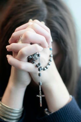Young woman praying the rosary. Paris. France.
